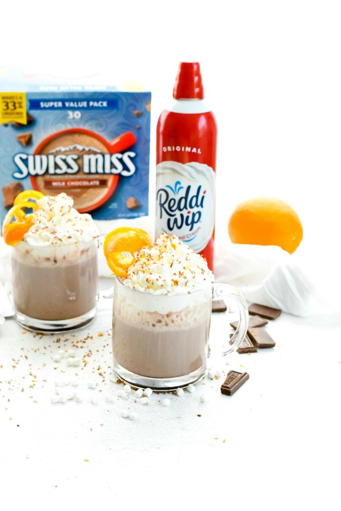 Orange Hot cocoa recipe in glass mugs with cocoa box and whipped cream can in the background.
