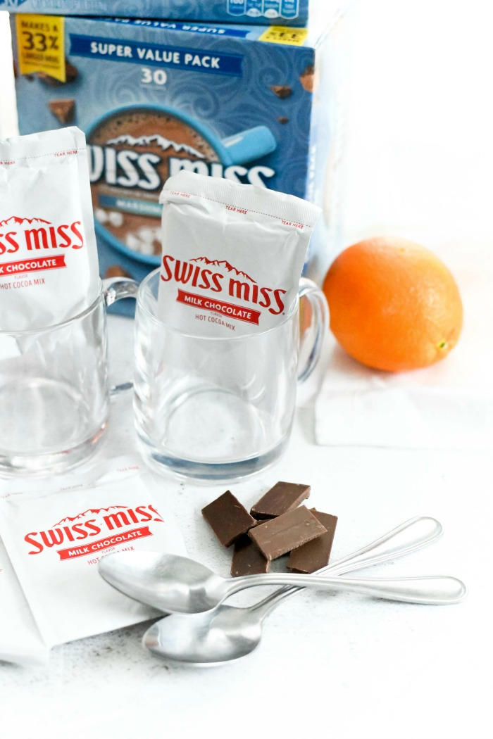 Hot cocoa packets in glass mugs with chocolate pieces and an orange on a white table.