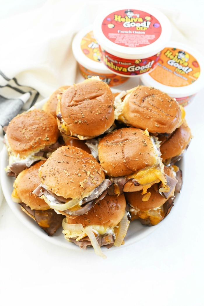 Cheddar and roast beef sliders on platter with dip.