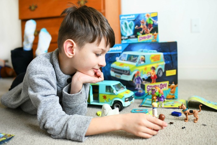 Boy playing with Scooby Doo Playmobil toys on carpet.