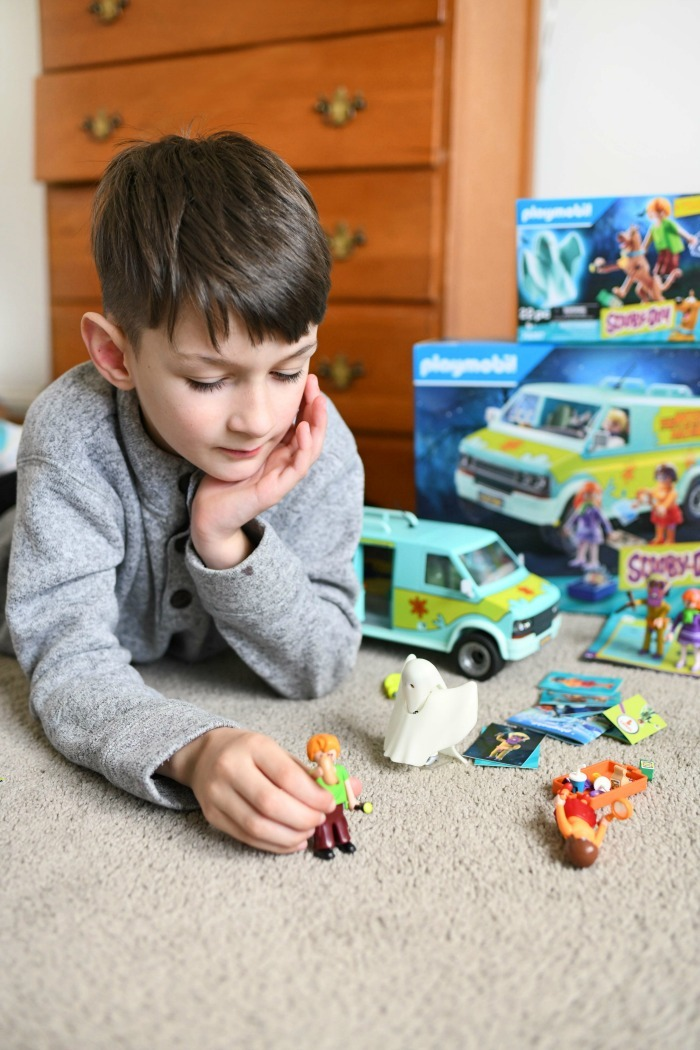 Little boy playing with Scooby Doo toys on carpet.