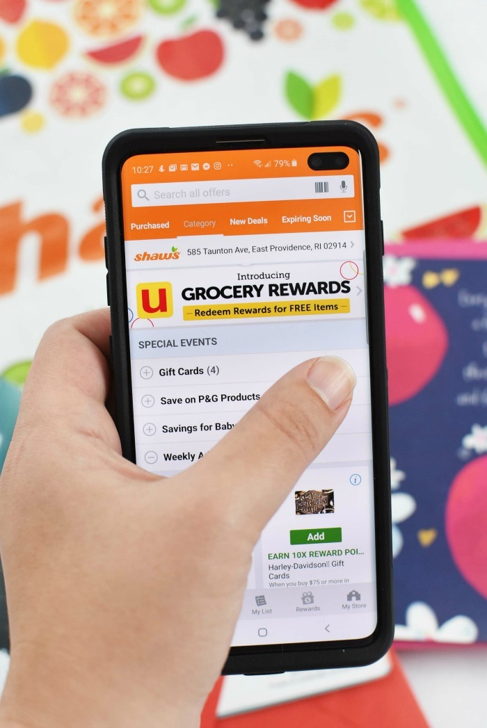 Shaws Rewards app in a lady's hand.