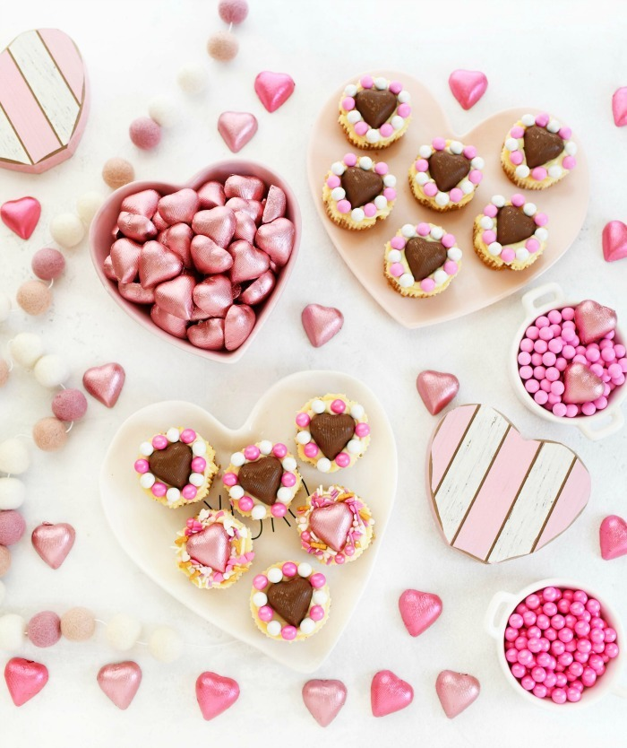 Valentine's Day cheesecakes and chocolates with hearts on a white table.