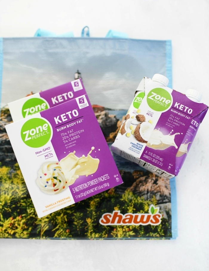 Zone perfect keto shake and powder on table with Shaw's bag.