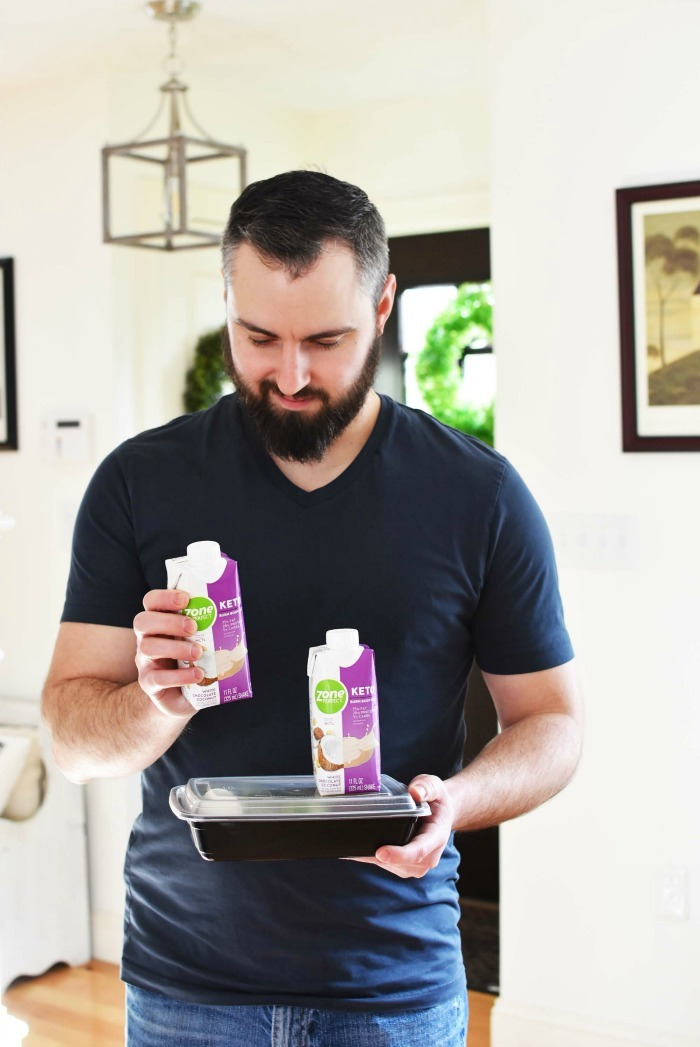 Man with ZoneKeto shake in his hand in living room.