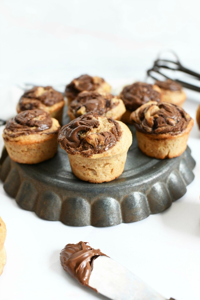 Nutella banana muffins on upside down pie dish tin with a Nutella lined knife.