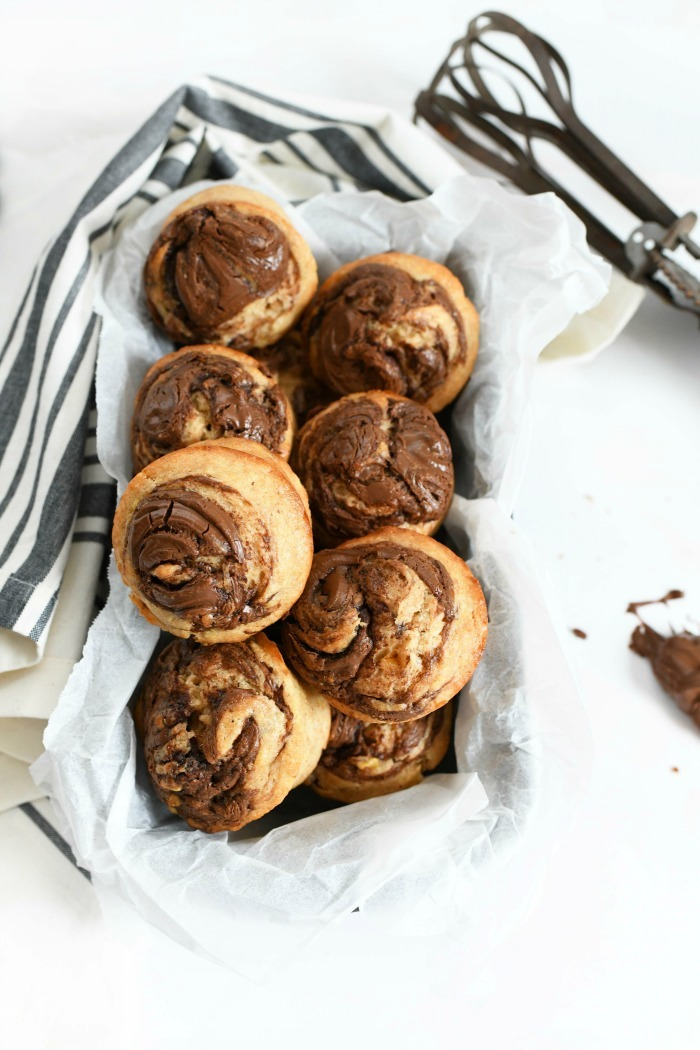 Nutella banana muffins in parchment lined baking tin. A grey-striped napkin is nearby.