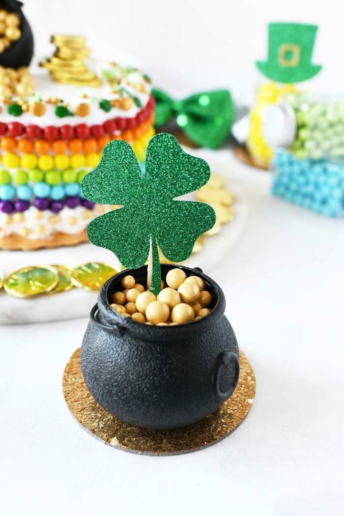 Pot of gold with candy gold balls and a glittery shamrock cupcake topper.