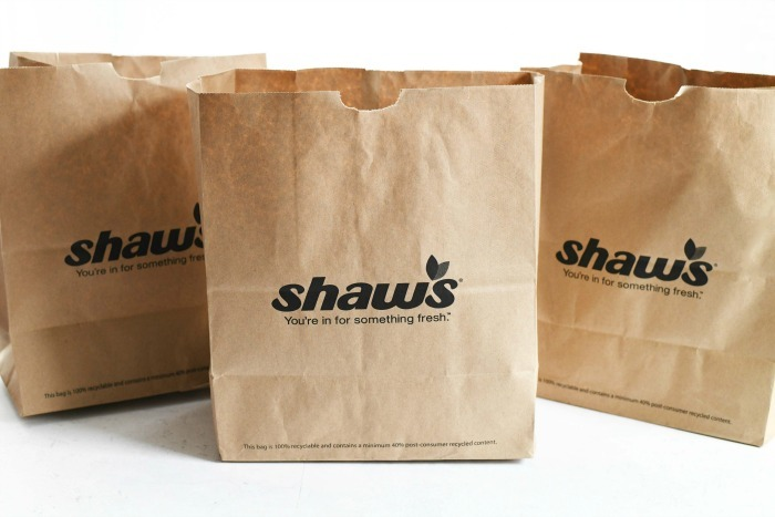 Shaws paper bags on white table.