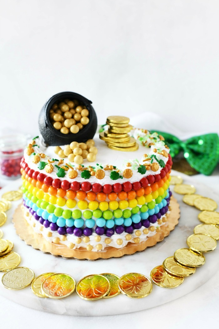 St Patrick's Day rainbow cake with coins on a platter.