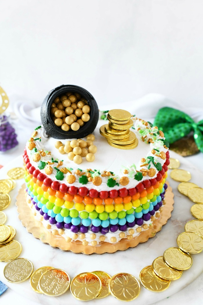 St Patricks Day Cake finsihed on the tray with rainbow and gold candies.