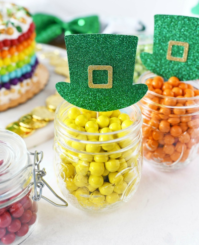 St Patrick's day candies in little glass jars with leprechaun cupcake toppers.