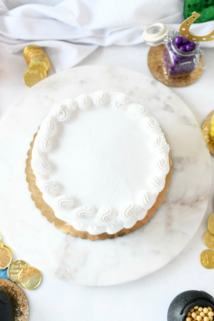 White plain cake on a circular marble tray.