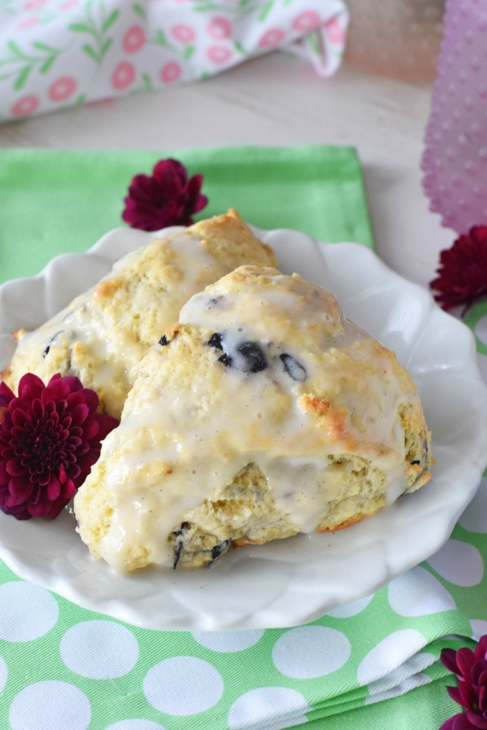 Blueberry Vanilla Scones Recipe on a white flowered plate with a green napkin and purple flowers.