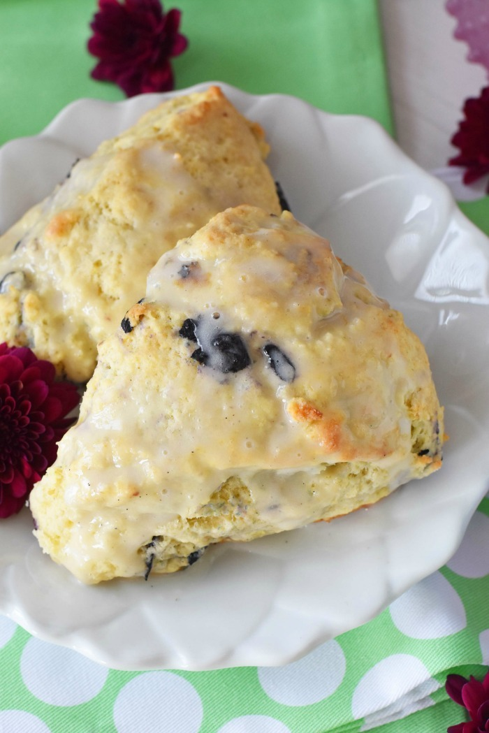 Blueberry scones on a white flowered plate with a green napkin and purple flowers.