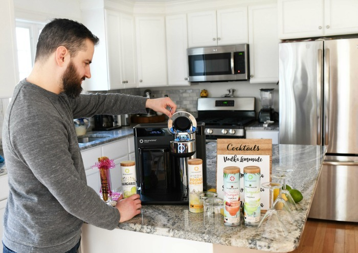 Man using a Drinkworks Cocktail maker in white kitchen.