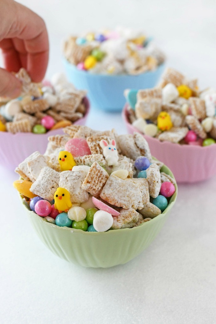 Easter Bunny Bait in pastel dishes with hand taking some mix out.