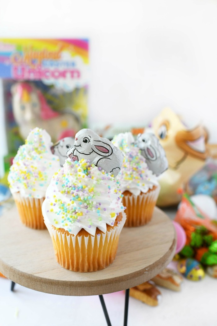 Easter Bunny Cupcakes with sprinkles on wooden stand.