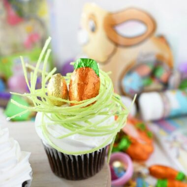 Easter Egg in Grass Cupcakes on a wooden platter.