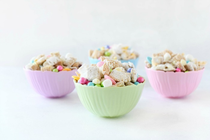 Easter Muddy Buddies mix in pastel dishes.