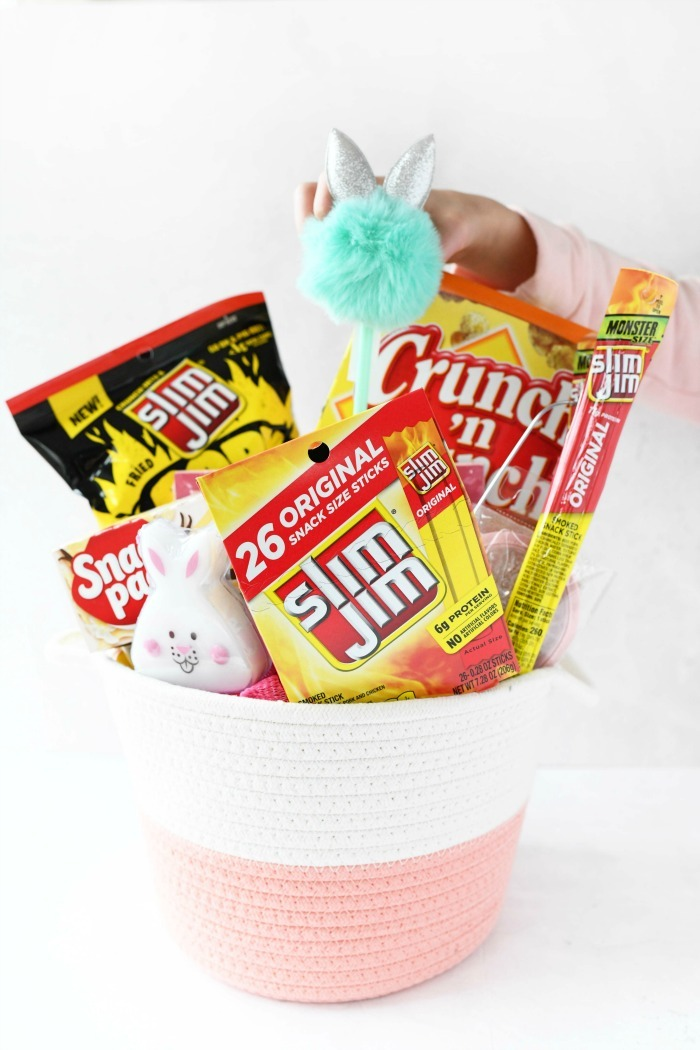 Easter basket stuffed with snacks like slim Jim. Girl is putting a fluffy green pen inside.