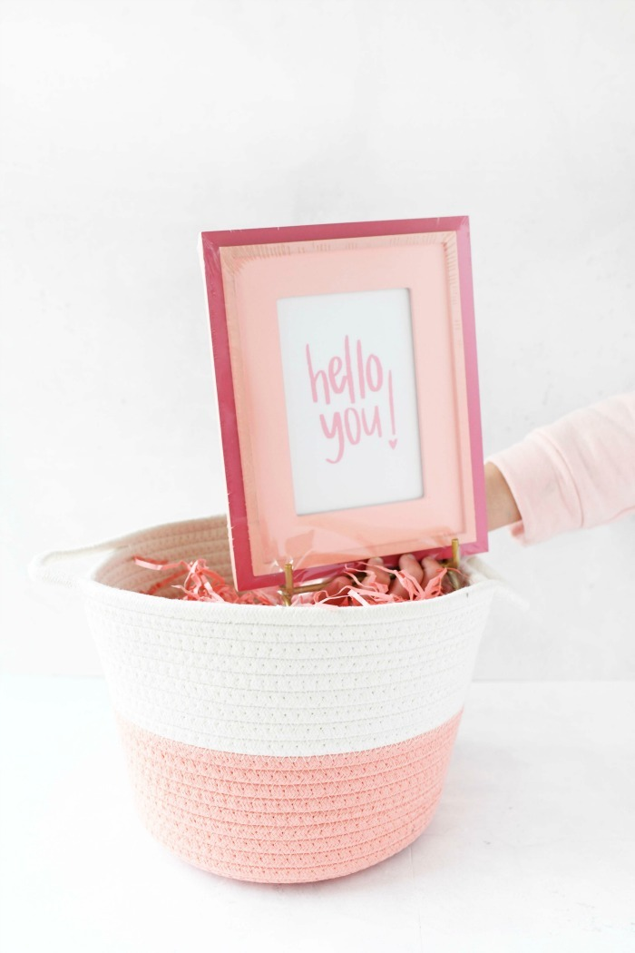 Hello You pink framed sign going into a pink Easter basket.