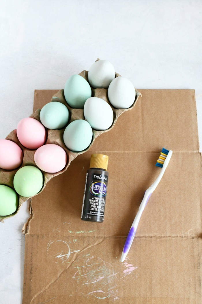 Egg speckling craft supplies on cardboard lined table.