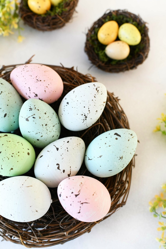 DIY pastel speckled eggs in wooden nest.