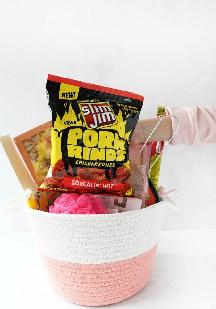 Slim Jim Pork Rinds going into pink Easter basket.