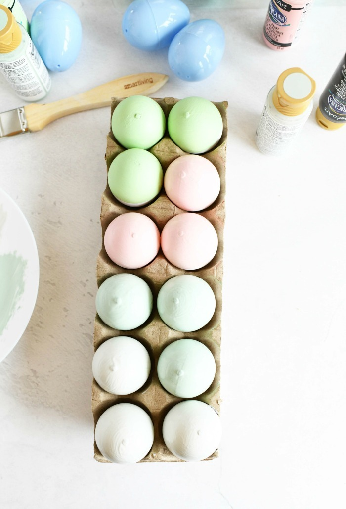 Pastel painted farmhouse style  craft eggs on white table with supplies scattered around.