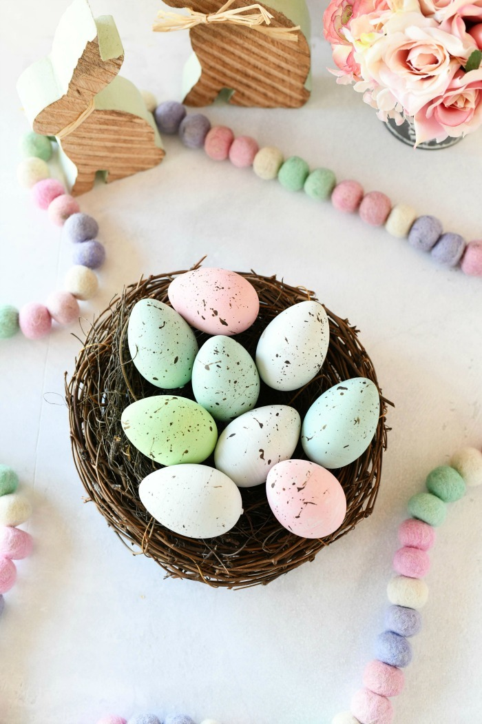 Painted speckled eggs in a nest on a white table.