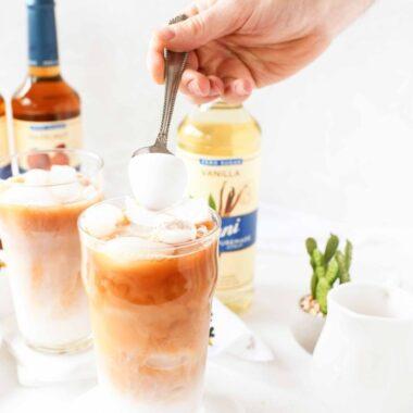 A man putting almond milk foam on an iced tea latte.