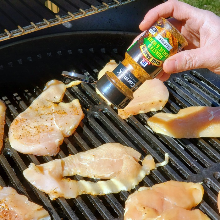 Chicken being seasoned on the grill with McCormick spice.