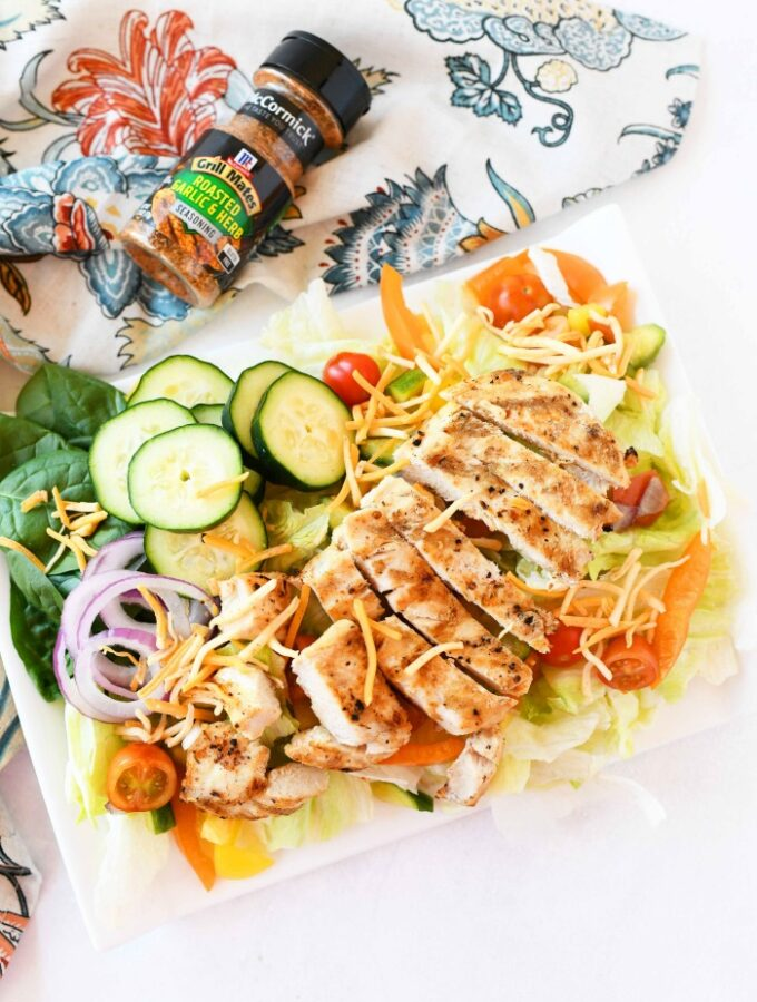 Grilled Chicken on salad on white plate with patterned napkin