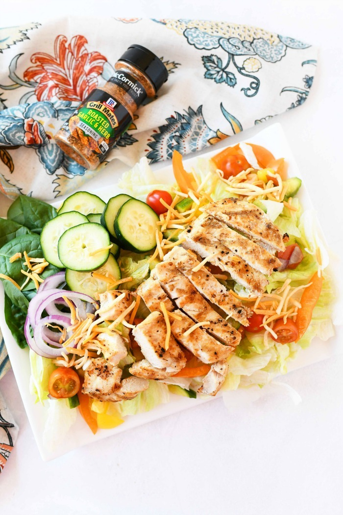 Grilled Chicken on salad on white plate with patterned napkin. A McCormick Spice bottle is nearby.