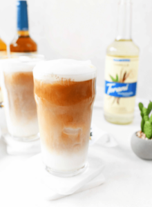 Iced tea latte in glass on white background