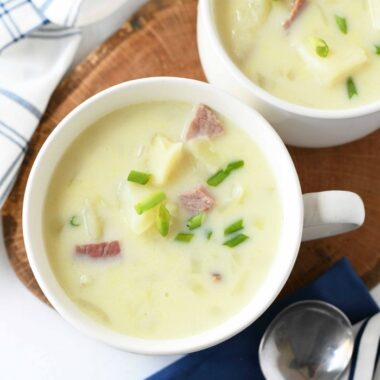 Spiral Ham Potato Soup with blue napkins and silver spoons.