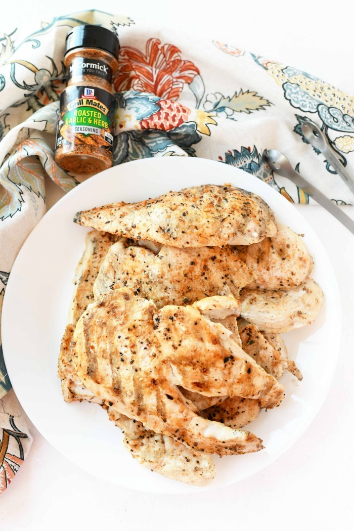 Fully seasoned, grilled chicken on white plate.