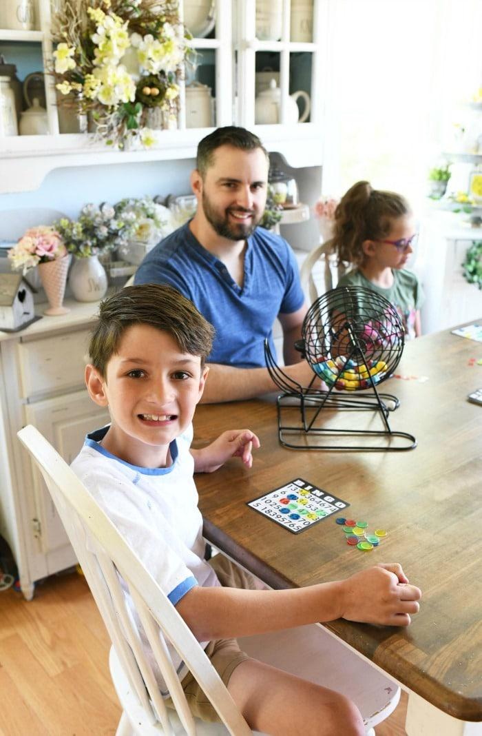 Family smiling at table playing bingo.