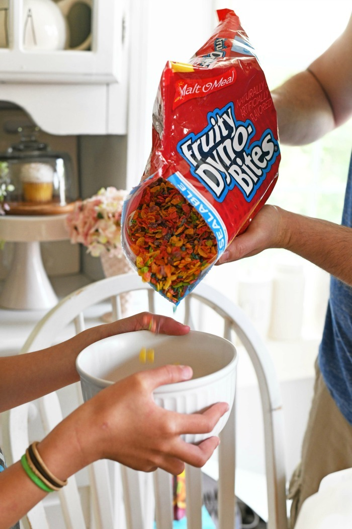 Fruity Dyno Bites Cereal pouring into a white bowl.