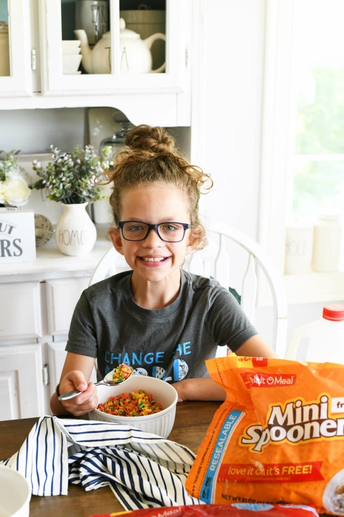 Girl eating cereal at a table smiling.
