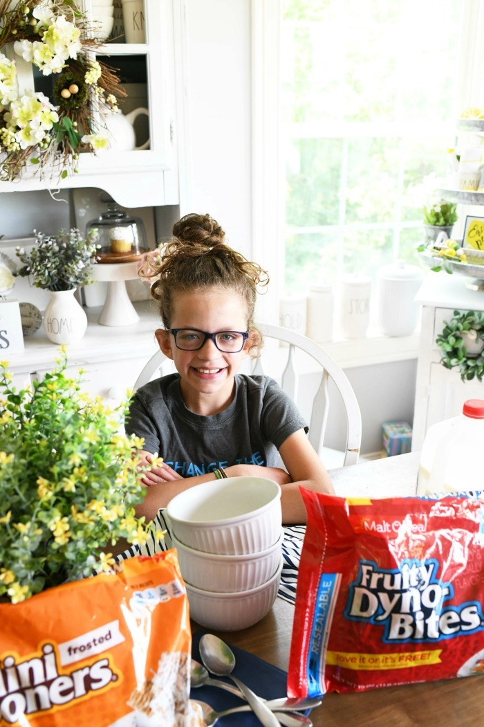 Girl with Malt o Meal cereal smiling at a table.