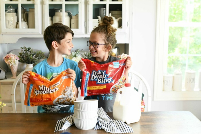 Kids with cereal smiling bags in kitchen.