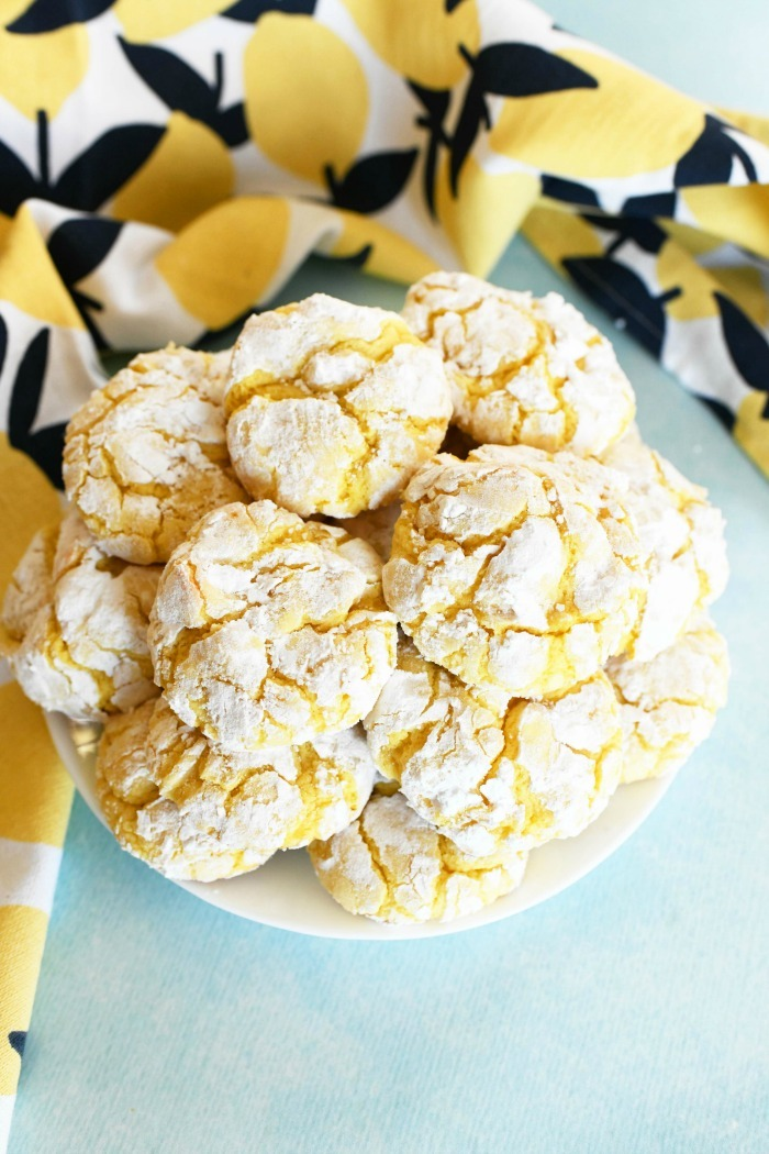 Lemon crinkle cake cookies on a white plate on a blue surface.
