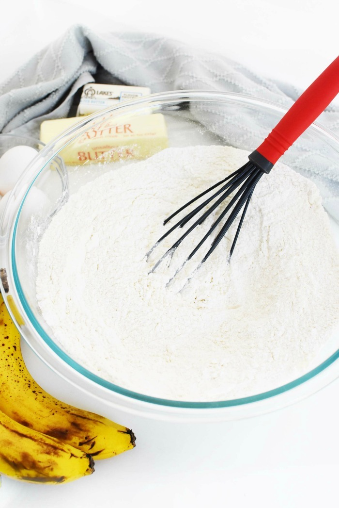 mixing bowl with batter and ripe bananas on a white table.