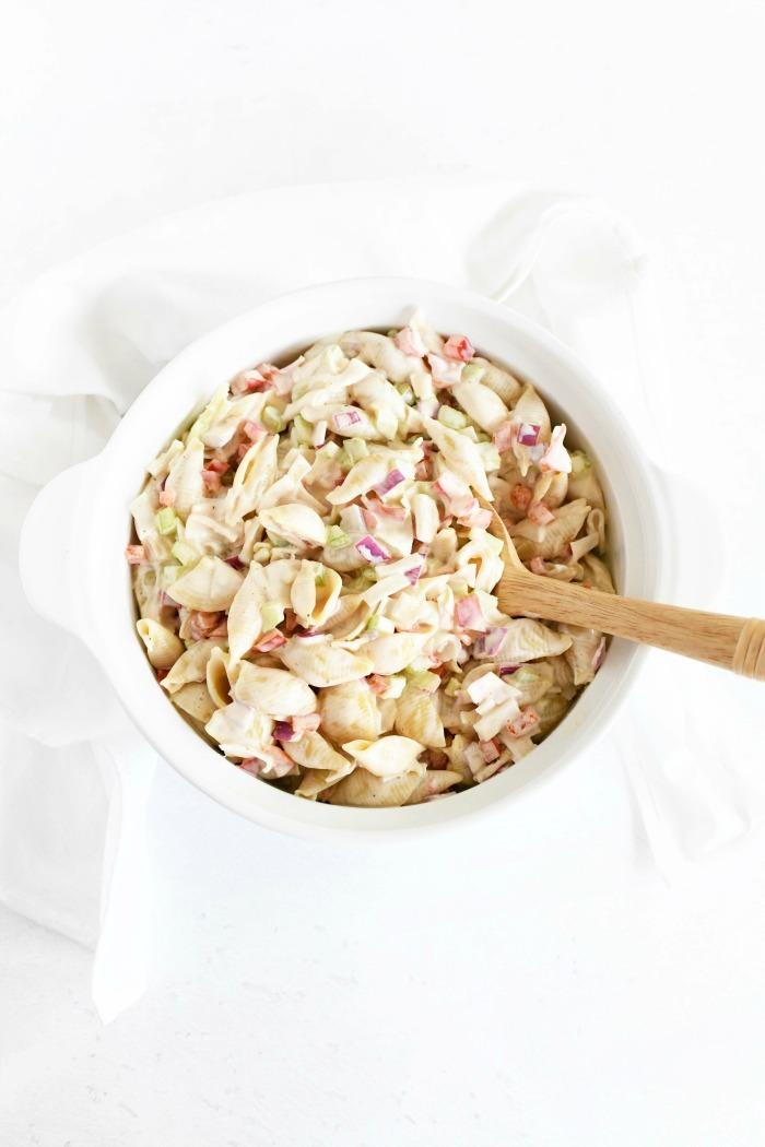 Crabmeat pasta salad in white dish on a white table. Dish is surrounded by a white napkin.