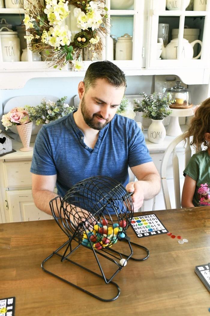 Father rotating bingo machine at table.