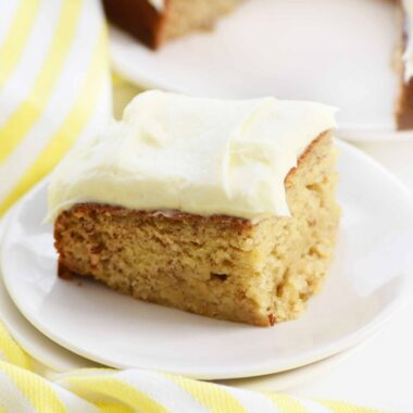 Frosted banana cake on white dish with yellow linen towel.