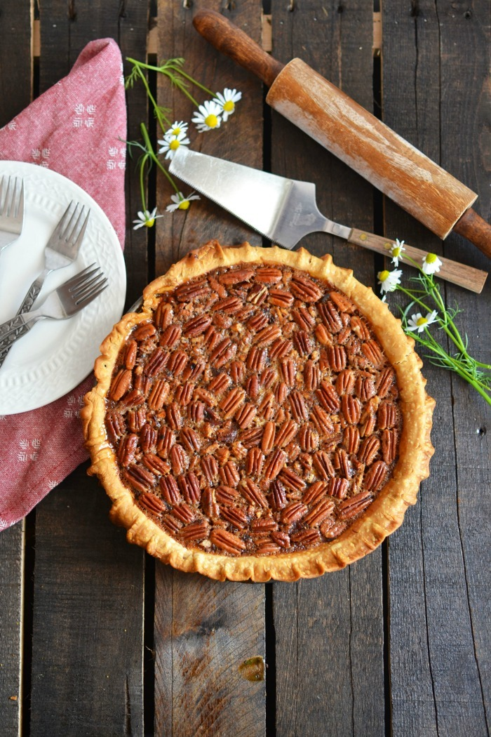 Baked Pecan Pie on wooden table with server.
