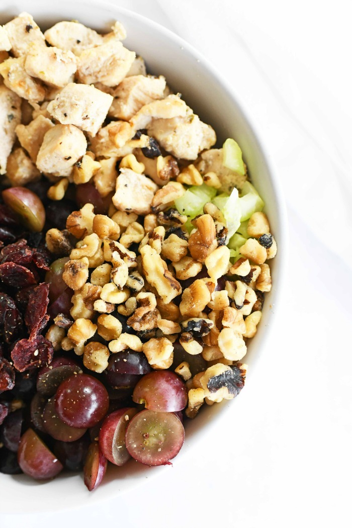 Chicken salad with grapes and nuts in a white dish.